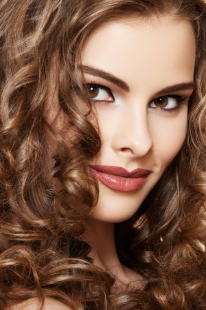Lovely model with shiny volume curly hair  Pin-up style on beige background  photo