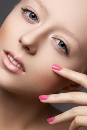 Beautiful young model with natural make-up and bright pink manicure  Wellness  Close-up beauty portrait of lovely european woman with clean healthy skin, pale lips photo