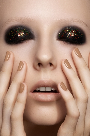 Beauty close-up portrait of sexy model woman with dark smoky eye make-up, bright glitter on eyelids, perfect beige nails polish photo