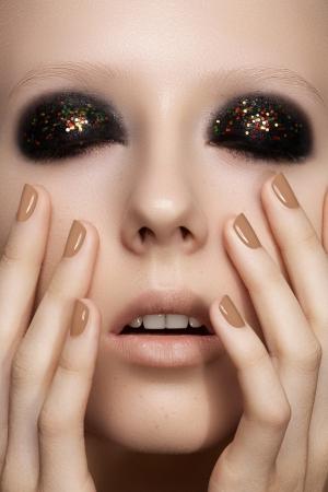 Beauty close-up portrait of sexy model woman with dark smoky eye make-up, bright glitter on eyelids, perfect beige nails polish Stock Photo