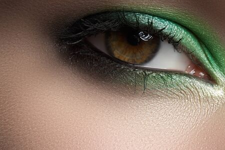 Elegance close-up of female eye with green smoky eye shadow  Macro shot of face part  photo