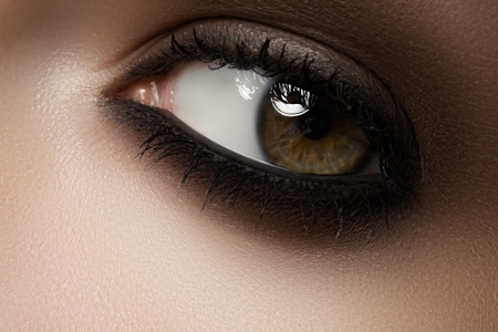 Elegance close-up of female eye with classic dark brown smoky make-up photo