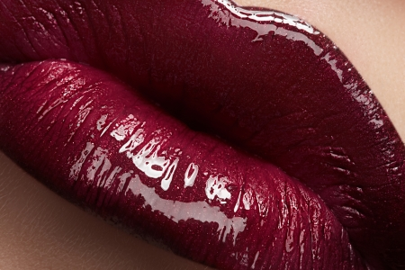 Close-up of woman s lips with bright fashion dark red glossy make-up  Macro lipgloss cherry make-up  photo