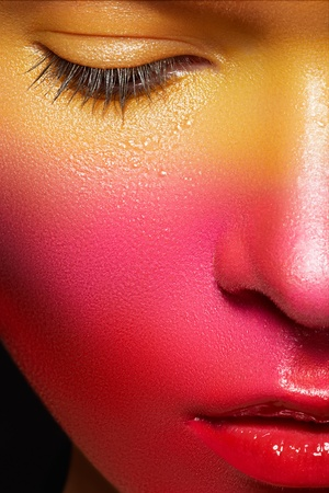 Beauty close-up portrait of beautiful woman model face with magic creative fashion multicolored make-up photo