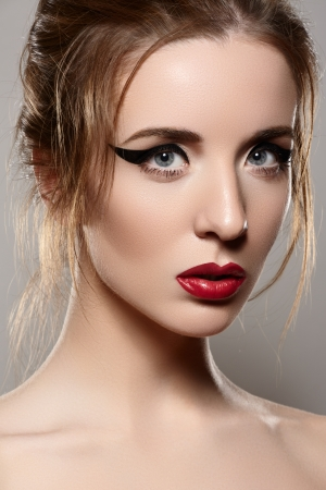 Close-up portrait of sexy caucasian young woman model with glamour red lips make-up, eye arrow makeup, purity complexion  Perfect clean skin   photo
