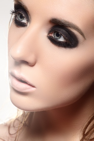 slicked: Luxury woman model with dark evening smoky eyes make-up on gray background  Stock Photo
