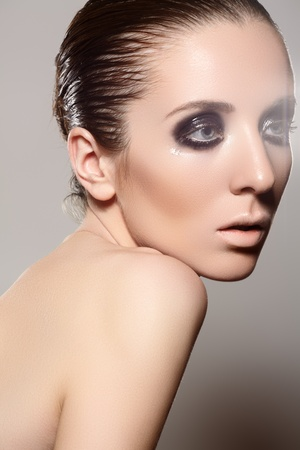 slicked: Luxury woman model with dark evening smoky eyes make-up, slicked hairstyle on gray background