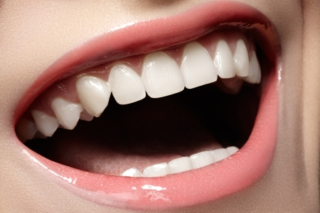 stomatology: Macro happy woman s smile with healthy white teeth, tender pink gloss lips make-up  Stomatology and beauty care