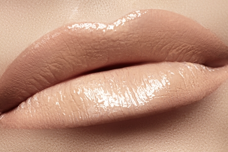 Close-up of woman s lips with fashion natural beige lipstick makeup  Horizontal macro sexy pale lipgloss make-up  photo
