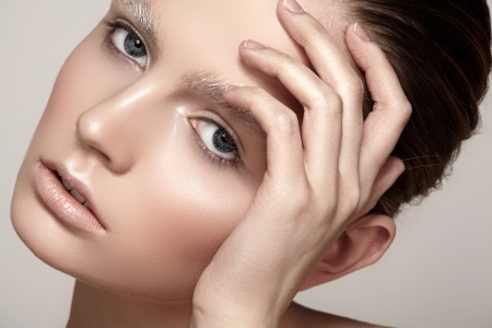 Amazing fashion winter make-up with bright shiny skin, pale lips, sparkles eyebrows  Beautiful christmas celebratory woman look Stock Photo - 19509031