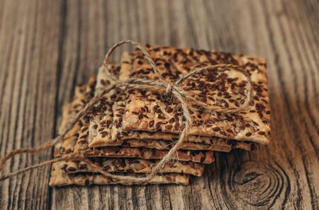 Healthy fresh baked crackers on the wooden table. Close up. Bowknot of twine rope. Sunflower seeds and flaxseed. Column