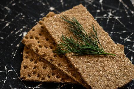 Rye breads lie on a black background. Crispbread. Diet