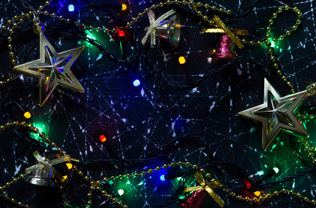 Decorations of a Christmas tree in the shape of stars on a black background. The included electric garland. Christmas lights Banco de Imagens