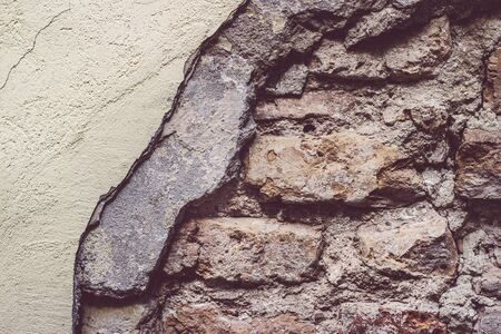 Fragment of the old brick wall under the plaster