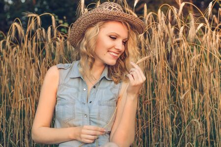 Beautiful smiling girl looks at a spike of rye. Young woman holding a rye spike in her hands. A field of wheat
