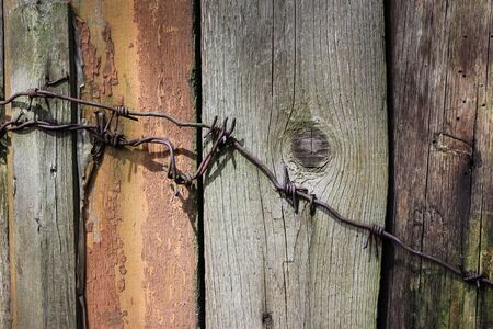 Old fence with cracked paint, rusty nails and wire