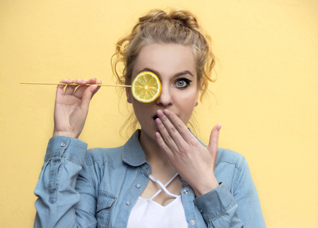 The beautiful girl is surprised covers his mouth with his palm. On a yellow background with a lemon in his hand.