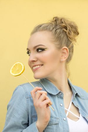 A beautiful girl with a yellow make-up is holding a lemon in her hand like a lollipop. Vertical photo.