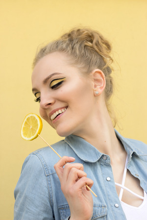A nice girl with bright makeup tilted her head and laughs. She holds a lemon in her hand Banco de Imagens