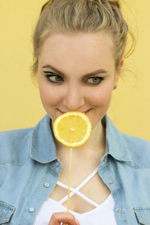 beautiful girl with bright yellow makeup. Holds the lemon as a lollipop.