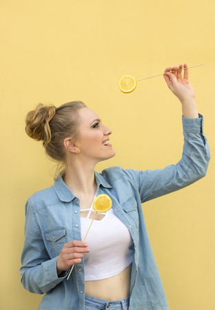 beautiful girl with two lemons. Bright, creative and happy. Portrait to the waist.