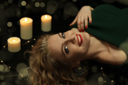 Beautiful young woman smiling. Looks up from the bottom. Red lips and nails. The festive atmosphere. Black background and flame of candles.