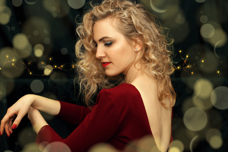 The beautiful woman sitting on a background of garlands and lights. Evening Dress. Naked back. Red lips, nails and dress.