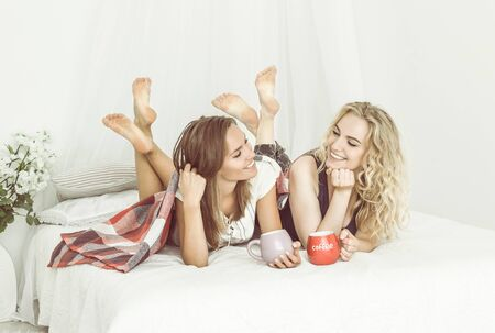 Girls pajamas party with coffee. The girls lying on bed and laughing. Two young attractive women are having fun at home in bedroom