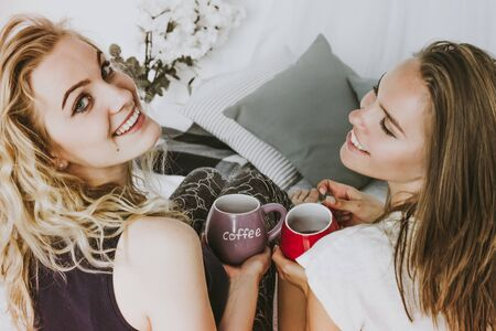 Two girls are smiling while holding cups of coffee in their hands. Hen party with cups of coffee at home.   looking at camera