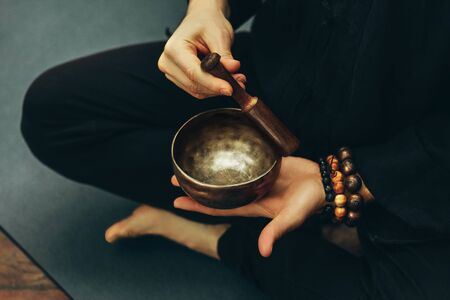 top view of a man sitting in a lotus position with a rosary on his hand playing on singing bowls. Relaxation and meditation. Alternative medicine. Tibetan and Himalayan singing bowls. Making sound.