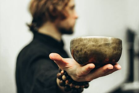 A man holds a singing bowls on his outstretched hand. Music of Tibetan singing bowls. Himalayan bowls. Making sound. Stock Photo