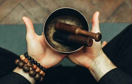 Close-up two hands of a man holding singing bowls with sticks in front of him. Listen to the healing vibrations of Tibetan bowls. Humility and calm. Rosary on the hand