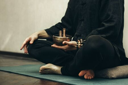 Сlose-up A man sits with his legs folded and holding a copper singing bowl with sticks in his hands. Relaxation and meditation. Alternative medicine. Tibetan and Himalayan singing bowls. Make a sound.