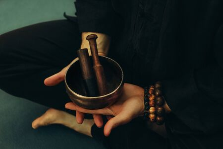 Top view of two hands of a man holding a singing bowl with sticks in front of him. Listen to the healing vibrations of Tibetan bowls. Humility and calm. Rosary on the hand. Close-up