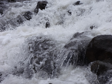 source: A creek full of rushing water from melting snow Stock Photo