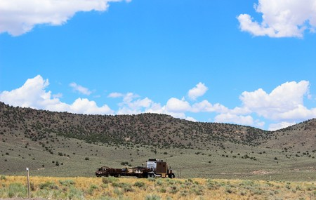 american field service: A highway runs through the desert highlands in the Western US
