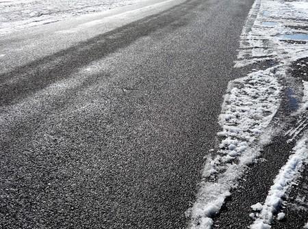 winter tires: Sun melting snow on an icy street
