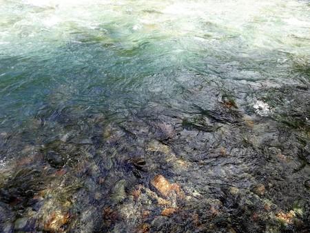 Koud waterstroom met witte plons aan de rand van een bergbeek stroomversnelling