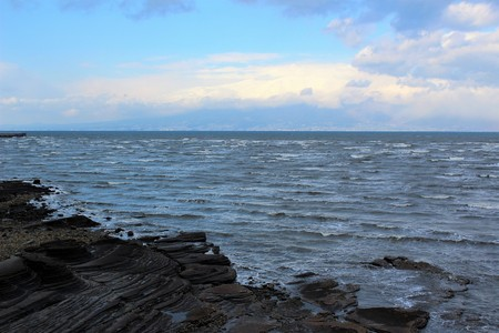 Storm clouds hanging over Shimabara town across the rough waves of Shimabara Bay in winter