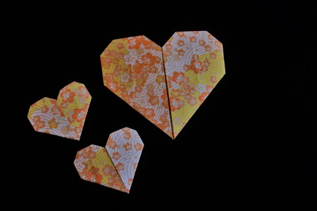 Traditional flower print Japanese origami hearts on a black background Banque d'images