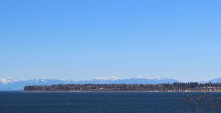 Wintery scene of deep blue Birch Bay and snow covered Canadian Coastal Mountain range