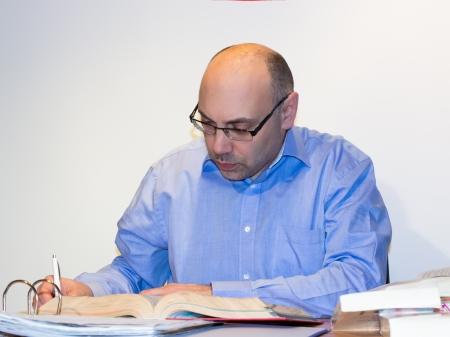 Man writing at a desk Stock Photo
