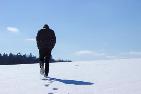 Uomo che corre nella neve Archivio Fotografico