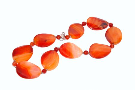 amber coloured: Red beads from semiprecious stones on a white background Stock Photo