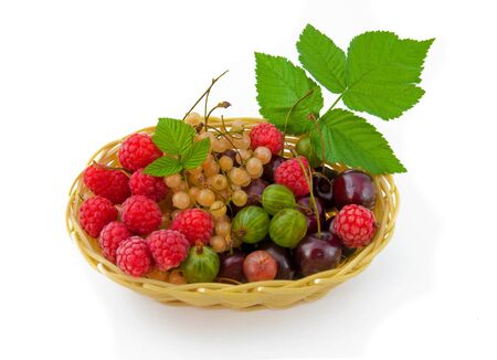 Basket with a raspberry, a cherry and a gooseberry, green leaves Stock Photo - 10009786