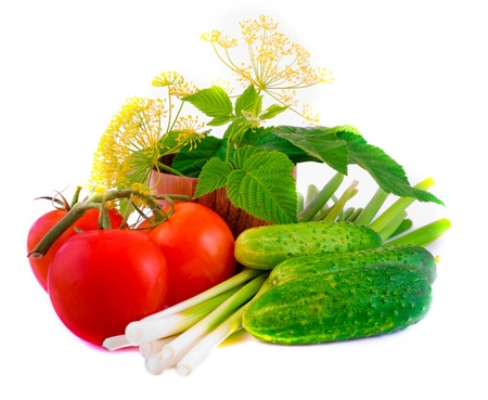 Still-life from a tomato, a cucumber, and onions with a flower and green leaves photo