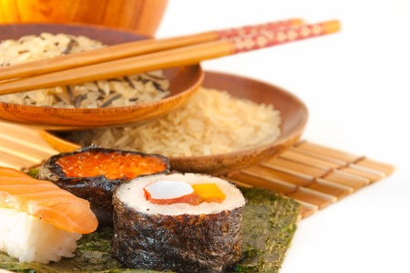 Rice in wooden plates plates, a Japanese fan and yellow stick for a sushi photo