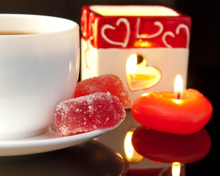 Cup of coffee and candle in the form of heart on a black background photo