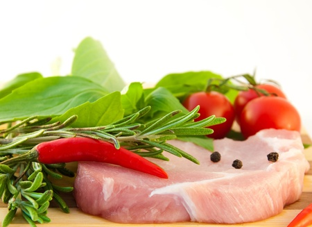 Meat, tomatoes, a basil and pepper against a wooden board Stock Photo