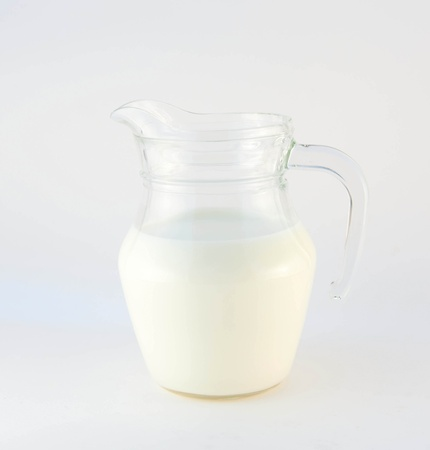 Jug of fresh cow milk on a white background